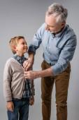 Älterer Mann knöpft Hemd des glücklichen Enkels auf grau