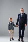 Reifer Geschäftsmann hält Hand seines Enkels, während er auf grau läuft