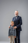 glücklicher Geschäftsmann in formeller Kleidung umarmt Schultern seines Enkels, während er isoliert auf grau in die Kamera blickt