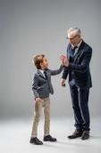 glücklich reifer Geschäftsmann gibt hoch fünf zu Enkel auf grau