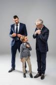 Lächelnder Geschäftsmann mit Blick auf Großvater und Enkel, die graue Krawatten anrühren