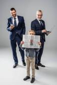 Lächelnde Geschäftsleute in offizieller Kleidung halten Gadgets in der Hand und schauen einen Jungen mit Zeitung auf grau an