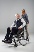 Älterer Mann im Rollstuhl sieht lächelnden Enkel auf grau