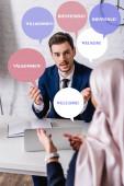 Fotografie Dolmetscher im Gespräch mit arabischem Geschäftspartner im verschwommenen Vordergrund, Sprechblasen mit Begrüßungswort in verschiedenen Sprachen Illustration