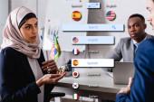 arabian businesswoman talking to interpreter near african american business partner, translation app interface illustration
