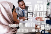 arabian businesswoman near multicultural business partners on blurred background, welcome word in different languages illustration