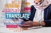 Ausgeschnittene Ansicht des arabischen Dolmetschers, der auf dem Laptop tippt, Schriftzüge in Wortnähe in verschiedene Sprachen übersetzt. Übersetzung: willkommen