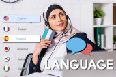Photo smiling arabian interpreter in headset holding digital translator on blurred foreground, speech bubbles near icons with different languages illustration