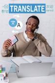 africký americký tlumočník držící digitální překladač, ikony se šipkami v blízkosti slov v různých jazycích. Překlad: Přeložit