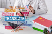partial view of interpreter holding digital translator and writing in notebook, translate lettering near words in different languages illustration. Translation: welcome