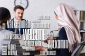 smiling translator near multicultural business partners on blurred foreground, word welcome in different languages illustration