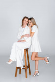 full length of young daughter standing near mother sitting on stool on grey