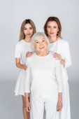mother and daughter near smiling grandma on grey, generation of women