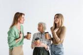 drei Generationen von Frauen, die Pappbecher in der Hand halten und isoliert auf weiß streiten