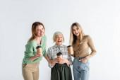 Fotografie drei Generationen fröhlicher Frauen mit Pappbechern auf weißem Grund