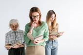 drei Generationen intelligenter Frauen in Brillen, die Bücher isoliert auf Weiß lesen