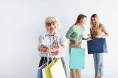Fröhliche Seniorin hält Einkaufstüten in der Nähe von Tochter und Enkelin auf verschwommenem Hintergrund