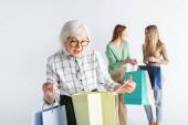 Fotografie Überraschte Seniorin blickt auf Einkaufstasche in der Nähe von Tochter und Enkelin vor verschwommenem Hintergrund