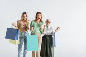 three generation of amazed women holding shopping bags isolated on white