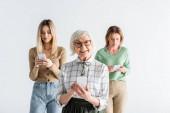 Fröhliche Seniorin mit Brille hält Smartphone in der Nähe von Tochter und Enkelin auf verschwommenem Hintergrund