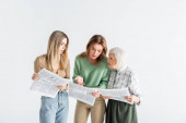 three generation of women reading newspapers isolated on white