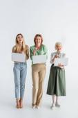 Drei Generationen fröhlicher Frauen, die mit den Fingern zeigen und Laptops auf weiß halten