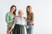 tři generace potěšených žen při pohledu na kameru izolované na bílém