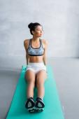 mladá africká americká žena ve sportovním oblečení dívá pryč, zatímco sedí na fitness podložka doma