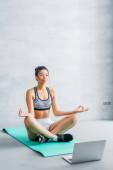 fiatal afro-amerikai nő sportruházatban meditál lótuszban pózol fitnessz szőnyegen laptop közelében