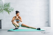 young african american sportswoman doing stretching exercise on fitness man near laptop