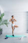 junge afrikanisch-amerikanische Frau in Sportbekleidung übt Lotus stehend neben Laptop zu Hause posieren