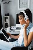 oldalnézet afro-amerikai szabadúszó vezeték nélküli fejhallgató kezében digitális tabletta üres képernyőn, homályos háttér