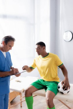 doctor writing prescription near injured african american football player sitting with ball on massage table