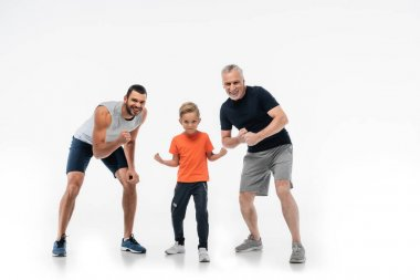 Boy with dad and grandfather in sportswear demonstrating strength while smiling at camera on white stock vector
