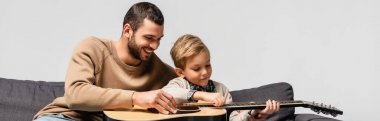 happy man teaching son playing acoustic guitar isolated on grey, banner