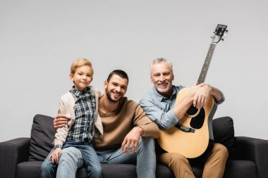 happy mature man with acoustic guitar sitting on sofa near son and grandson isolated on grey
