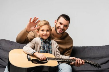 cheerful boy playing acoustic guitar near happy father waving hand at camera isolated on grey