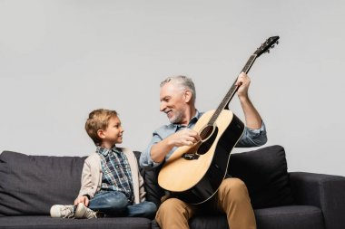 happy grandfather playing acoustic guitar near smiling grandson isolated on grey