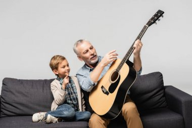 mature man pointing with finger at acoustic guitar near grandson isolated on grey