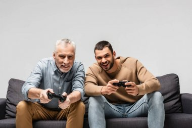 KYIV, UKRAINE - NOVEMBER 17, 2020: cheerful father and son playing video game with joysticks isolated on grey stock vector