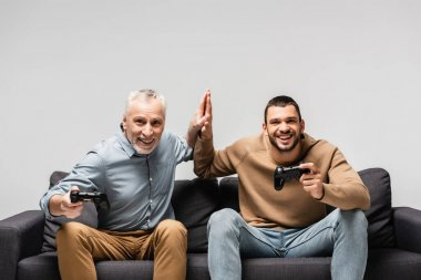 KYIV, UKRAINE - NOVEMBER 17, 2020: excited father and son giving high five while sitting on sofa with joysticks isolated on grey stock vector