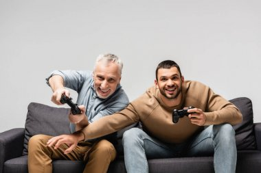 KYIV, UKRAINE - NOVEMBER 17, 2020: excited father and son playing video game on sofa isolated on grey stock vector