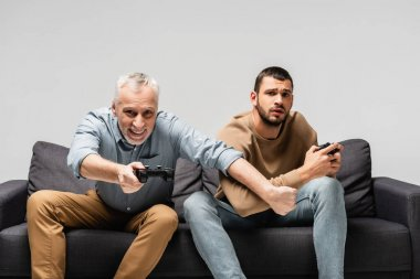 KYIV, UKRAINE - NOVEMBER 17, 2020: happy man playing video game near upset son isolated on grey stock vector