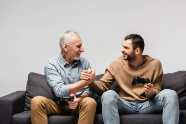 KYIV, UKRAINE - NOVEMBER 17, 2020: cheerful father and son shaking hands while holding joysticks isolated on grey stock vector