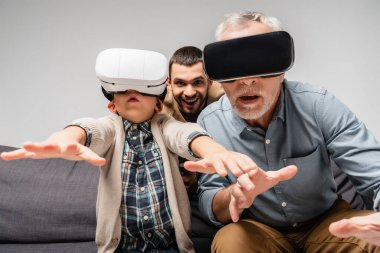 Grandfather and grandson gesturing in vr headsets near excited man on background isolated on grey stock vector