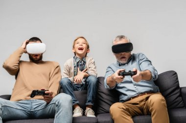 KYIV, UKRAINE - NOVEMBER 17, 2020: excited boy laughing near dad and grandfather playing video game in vr headsets isolated on grey stock vector