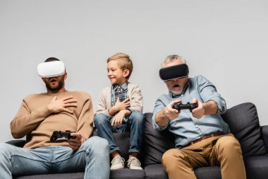 KYIV, UKRAINE - NOVEMBER 17, 2020: cheerful boy near scared dad and grandfather playing video game in vr headsets isolated on grey stock vector