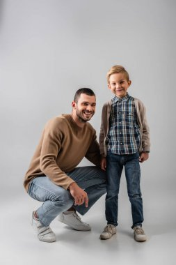 Happy father squatting near cheerful son while smiling at camera together on grey stock vector