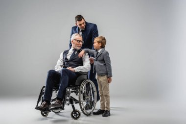 smiling man in formal wear standing near son and father in wheelchair on grey