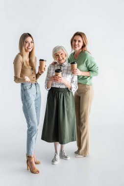 Full length of three generation of happy women holding paper cups on white stock vector